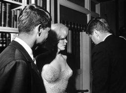 ...露在某派对上和约翰·F·肯尼迪说话,而罗伯特·F·肯尼迪(左)...