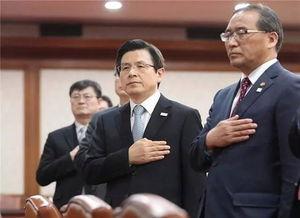 代行总统职权的国务总理黄教安(右二)在内阁会议上向国旗致敬.
