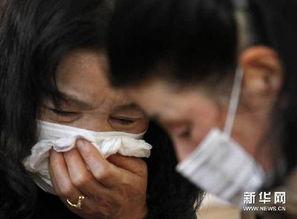 3月18日,在日本北部陆前高田的一座避难所内,一名在灾难中失去丈夫的妇女(左)在遇到自家亲属时哭泣。